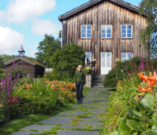 Lange staudebed foran eldre bygning, med Anne